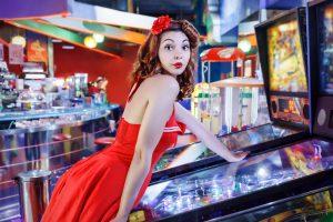 woman playing pinball machine
