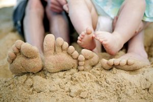 family feet on sandy beach